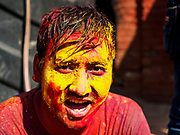 12 MARCH 2017 - BHAKTAPUR, NEPAL: A man with yellow and red powder on his cheek at a Holi celebration in Bhaktapur. Holi, a Hindu religious festival, has become popular with non-Hindus in many parts of South Asia, as well as people of other communities outside Asia. The festival signifies the victory of good over evil, the arrival of spring, end of winter, and for many a festive day to meet others. Holi celebrations in Nepal are not as wild as they are in India.     PHOTO BY JACK KURTZ
