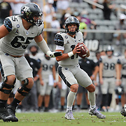 ORLANDO, FL - OCTOBER 24:  Quarterback Dillon Gabriel #11 of the Central Florida Knights looks on as he is protected by offensive lineman Cole Schneider #65 of the Central Florida Knights against the Tulane Green Wave at Bounce House-FBC Mortgage Field on October 24, 2020 in Orlando, Florida. (Photo by Alex Menendez/Getty Images) *** Local Caption *** Dillon Gabriel; Cole Schneider