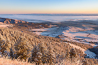 The light of sunrise illuminates one of the first snowfalls of the season in the Bighorn Mountains near Dayton. The switchbacks of Highway 14 can be seen in the valley.