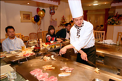 Japanese chef prepares sushi for diners on a central hot plate in Japanese restaurant Newcastle UK