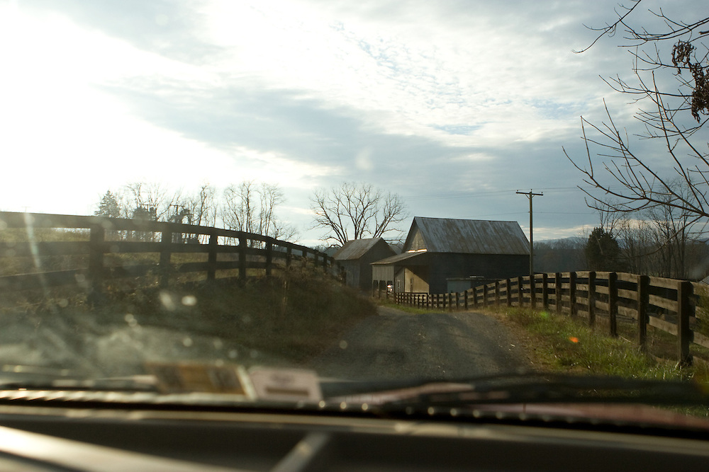Photograph taken from the passenger seat of an automobile driving on a road through two fenced-in fields that leads up to a farmhouse and barn.