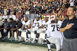"""Oakland Raiders players including offensive tackle Vadal Alexander (74), offensive tackle Marshall Newhouse (73), offensive guard Gabe Jackson (66), and Oakland Raiders offensive guard Jon Feliciano (76) sit on the bench and stare straight ahead as the national anthem is sung prior to the game against the Washington Redskins at FedEx Field in Landover, Maryland on Sunday, September 24, 2017. The Raiders chose to demonstrate prior to their nationally televised contest following tweets earlier in the day from United States President Donald J. Trump urging owners to """"fire or suspend"""" players who participated in the protests by not standing for the anthem. Photo by Ron Sachs/CNP/ABACAPRESS.COM"""