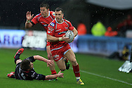 Gareth Davies of the Scarlets goes past  the tackle of Jeff Hassler of the Ospreys. Guinness Pro12 rugby match, Ospreys v Scarlets at the Liberty Stadium in Swansea, South Wales on Saturday 26th March 2016.<br /> pic by  Andrew Orchard, Andrew Orchard sports photography.