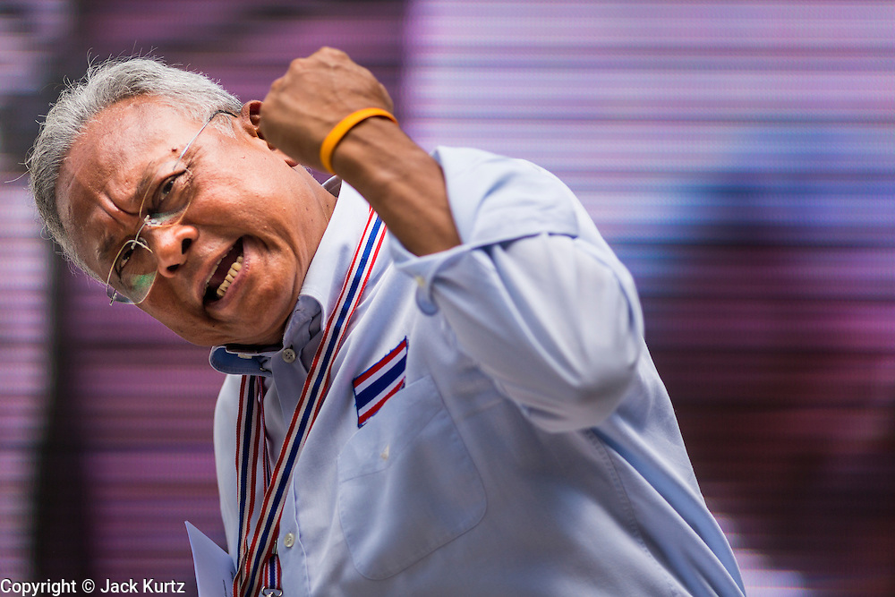 24 FEBRUARY 2014 - BANGKOK, THAILAND: Thai anti-government leader SUTHEP THAUGSUBAN on the Silom intersection stage Monday exhorts his followers to continue in their struggle against the government after several violent attacks on protestors' sites over the weekend. At least four people, three of them children, were killed in political violence over the weekend in Thailand. One in Trat province, near the Cambodian border, and three in Bangkok, at the Ratchaprasong protest site. At the Ratchaprasong site a grenade was fired into a crowd killing a child and an adult. A second child, injured in the blast, died overnight in a Bangkok hospital.   PHOTO BY JACK KURTZ