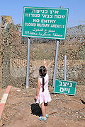Israel, Upper Galilee, Metula, (founded 1896) is situated on the Lebanese boarder. Young girl near a sign reading No Entry Closed military Area on the Lebanese border In Hebrew, English and Arabic Model Release Available