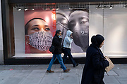 Londoners walk past a window of Primark that features three faces wearing face coverings, sold inside this high street retailer during the second (Autumn) wave of the Coronavirus pandemic, on 8th October, 2020, in London, England.
