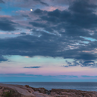 A waxing moon rises undeterred through a dramatic Maine sky.
