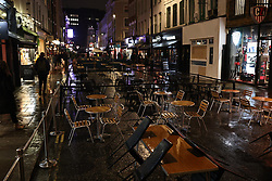 © Licensed to London News Pictures. 02/12/2020. London, UK. Mostly empty tables and chairs on a wet evening in Soho as pubs, bars and restaurants open after the end of the second England-wide lockdown. Photo credit: Rob Pinney/LNP