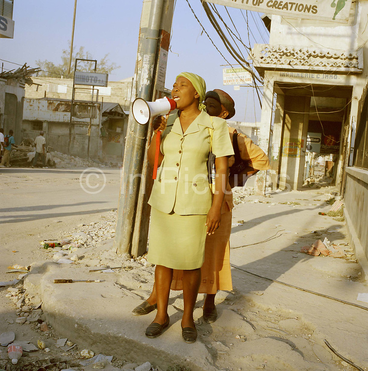 """This lady preaching in down-town Port au Prince says, """"you have to believe in God, this is God trying to send us a message."""" On Tuesday 12th of January at 16.53pm local time the biggest Earthquake to hit Haiti for 200 years struck with devastating force. 230,000 people were killed, 300,000 injured and 1.2 million left needing emergency shelter. Survivors have lost family, homes, livelihoods and essential services. Hospitals, schools and government buildings were also destroyed'. These pictures are of the survivors three weeks later."""