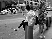 Two girls texting outside the Time Warner Center on Columbus Circle