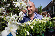 Man out shopping for plats at Columbia Road flower market, London. London's famous Sunday flower market on Columbia Road is always busy and people come here from the early hours to snatch up the best of the plants on offer, and latecomers also can snap up a few last minute bargains. Columbia Road os one of four local Sunday markets in this area of the East End of London.