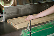 Female carpenter uses a powered carpenter's plane to flatten a plank of oak wood