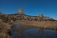 A moonlit Devils Tower is reflected in the Belle Fourche River near the campground.