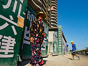 "15 FEBRUARY 2019 - SIHANOUKVILLE, CAMBODIA:  A Cambodian woman leaves the Blue Bay casino and resort construction site in Sihanoukville while a Chinese laborer carries materials into the site. There are about 80 Chinese casinos and resort hotels open in Sihanoukville and dozens more under construction. The casinos are changing the city, once a sleepy port on Southeast Asia's ""backpacker trail"" into a booming city. The change is coming with a cost though. Many Cambodian residents of Sihanoukville  have lost their homes to make way for the casinos and the jobs are going to Chinese workers, brought in to build casinos and work in the casinos.      PHOTO BY JACK KURTZ"