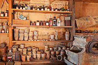 Chemical bottles and other supplies in the assay building at Cerro Gordo, a late 19th century mining community in the Inyo Mountains near Keeler, California. Newspapers on the wall are dated 1957 and 1959.