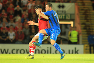 Harrison McGahey tackles Kieffer Moore during the EFL Sky Bet League 1 match between Rochdale and Barnsley at Spotland, Rochdale, England on 21 August 2018.