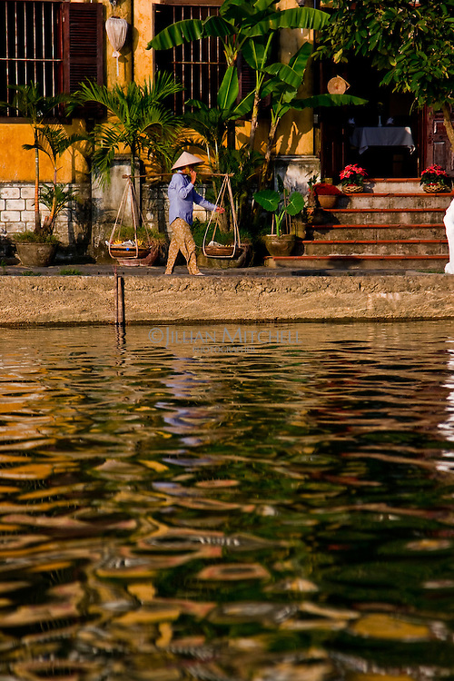 A street vendor wearing a conical hat walking along the Hoi An's waterfront lined with old french colonial architecture.