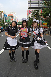 Young girls dressed in maids costume advertising nearby themed cafe in Akihabara Tokyo