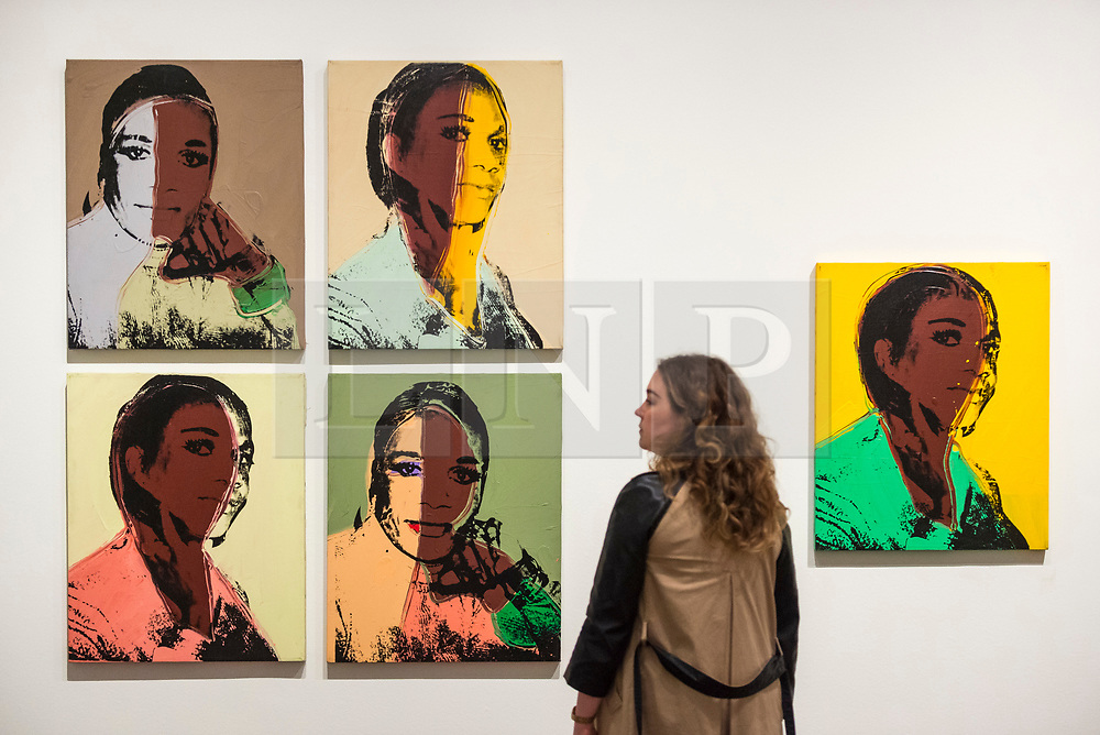 """© Licensed to London News Pictures. 10/03/2020. LONDON, UK. A staff member poses next to """"Ladies and Gentlemen (Alphanso Panell)"""", 1975, (images of New York black and latino drag queens and trans women) by Andy Warhol. Preview of """"Andy Warhol"""", a retrospective of over 100 works by one of the most recognisable artists of the late 20th century.  The exhibition runs 12 March to 6 September 2020 at Tate Modern.  Photo credit: Stephen Chung/LNP"""
