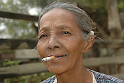 Myanmar Mandalay A female Villager smoking a cigarette along the Ayeyarwady River