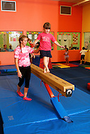 Kaitlyn Ray works with a student on the balance beam at The Little Gym in Brentwood on Saturday, May 19, 2012.  (Photo by Kevin Bartram)