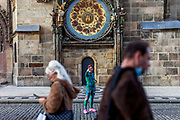 A female runner doing a selfportrait infront of the Astronomical clock at Old Town Square in Prague. As of 21st of October 2020 people have to wear face masks outside and inside except while doing physical activities as running or cycling.