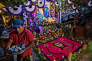 A Mexican man arranges ice cream cups to be given to visitors stopping to see the family altar celebrating El Viernes de Dolores during Holy Week March 23, 2018 in San Miguel de Allende, Mexico. The event honors the sorrow of the Virgin Mary for the death of her son and is an annual tradition in central Mexico.