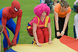 Spiderman and a clown  leading a parachute game with children at a Parklife summer activities event,
