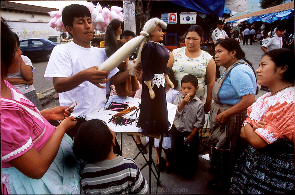 A traveling salesman selling hair ties uses a doll to show indigenous Guatemalan women how to tie their back with a new type of hair rolling band. Antigua, Guatemala. (image from the project Hungry Planet: What the World Eats.)