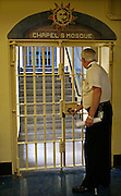 A prison officer locks the security gate to the prison chapel and mosque. HMP Wandsworth, London, United Kingdom