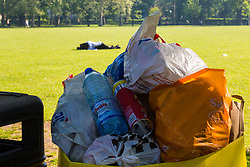A young couple canoodle on the grass as bags of litter surround bins in Queen's Park, North West London, following the hot, sunny Bank Holiday Monday which saw thousands descend on the capital's parks to enjoy the weather. London, May 08 2018.