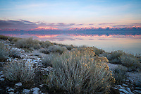 Sunset illuminates the mountains of Northern Utah as the last bit of light fades away over the Great Salt Lake as seen from Antelope Island on a cold Winter evening.