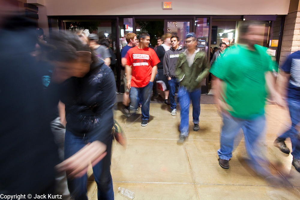 "24 NOVEMBER 2011 - PHOENIX, AZ:  People run into Paradise Valley Mall Thursday. The mall opened its doors a couple of minutes before the scheduled midnight opening.  ""Black Friday,"" the unofficial start of the holiday shopping season started even earlier than normal. Many stores, including Target and Best Buy, opened at midnight.    Photo by Jack Kurtz"