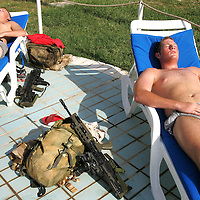 Baghdad, Iraq, 2 Oct 2005. Running 'Route Irish'...Rangers Paul Muirwood (left) and Sam Benson sunbathing at the 'Liberty Pool'.....B Company, 1st Battalion, The Royal Irish Regiment, a tight-knit multi national fighting force make daily escorting runs along ?Route Irish?, the infamous Baghdad Airport road. The 46 man team are all British Army regulars but come from as far afield as Fiji, South Africa and Northern and Southern Ireland. Previous deployments in Kosovo, Sierra Leone and Northern Ireland have equipped them with the valuable skills needed to provide protection for British Forces and materials transiting the world?s most dangerous highway. Due to an increased presence of US forces along the route both in dug in positions and mobile patrols, attacks along the road have slackened, despite this a day rarely passed without an IED (improvised explosive device) being detonated or a small arms attack against coalition forces. ..The convoy attempts to maintain a seclusion ?bubble? around its vehicles for the duration of the journey. Any civilian vehicle that either strays into the bubble or refuses to keep their distance represents a threat and should they ignore the warning blasts on air horns carried in each vehicle the rules of engagement progress from warning shots to use of lethal force. The relative safety of the International Zone offers them an opportunity to decompress between missions. A duty driver ferries soldiers to the ?Liberty Pool?. Once only frequented by Iraq?s Ba?athist elite the luxury swimming pool and gym now fills with troops. Their body armour, helmets and weapons all within easy reach they either soak up the sun or compete with each other in diving competitions. After a daily briefing the troops have access to the ?Mosquito and Camel? bar where they watch TV or play pool and in accordance with the ?2 can rule? are allowed to drink 2 beers per night.