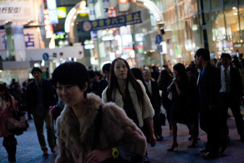 Street life in Tokyo - a woman is passing a huge crossing in the city centre. Tokyo has 13.01 million inhabitans, is the Japanese capital and the largest city in Japan. Tokyo, Japan, 20.10 2010. Tokyo, Japan, 22.10 2010.