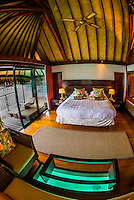 Interior view of a king panoramic overwater bungalow with a glass floor viewing panel, Hilton Moorea Lagoon Resort, island of Moorea, French Polynesia.