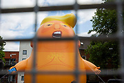 Trump Baby looks incarcerated behind bars as the Trump Baby sitting team give the six metre high inflatable TrumpBaby his second London outing in Bingfield Park, Kings Cross , London, United Kingdom. 10th July 2018. He WILL fly above Parliament Square in Westminster when the real Trump, president of the United States arrives in the United Kingdom on the 13th of July 2018.