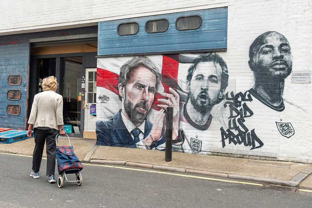 © Licensed to London News Pictures. 14/07/2021. London, UK. A woman walks past  the mural of England football team including manager GARETH SOUTHGATE and footballers HARY KANE and RAHEEM STIRLING has been unveiled near London. Bridge. The mural created by Marc Silver of MurWalls, is a celebration of a team that has united the nation. Photo credit: Ray Tang/LNP