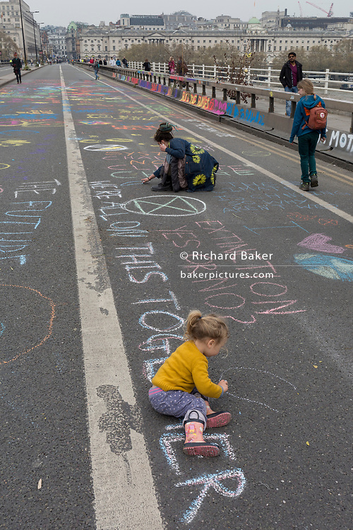 Shildren draw on the road as Climate Change activists with Extinction Rebellion campaign for a better future for planet Earth after blocking Waterloo Bridge and as part of a multi-location 5-day Easter protest around the capital, on 16th April 2019, in London, England.