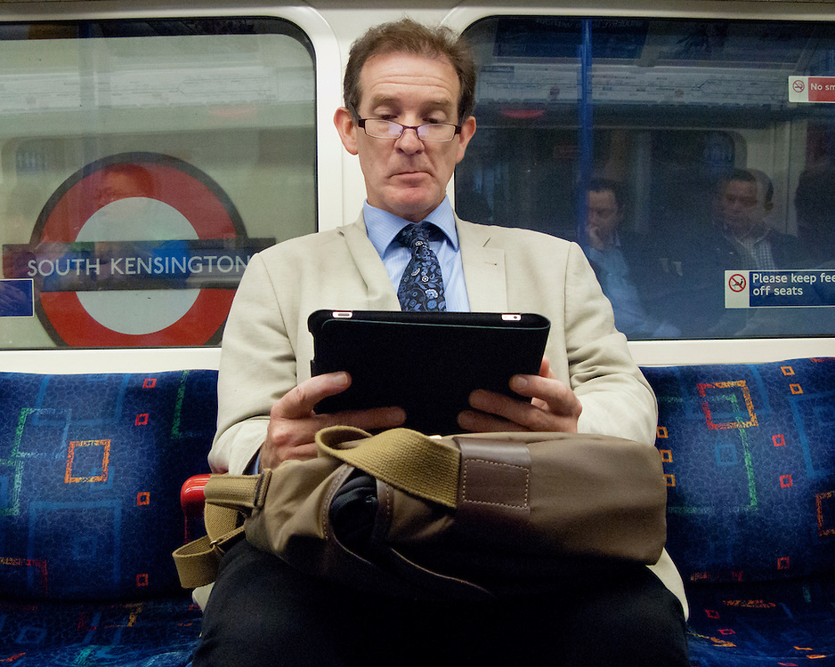 Portrait of a man on the London Underground reading an electronic device