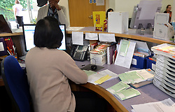 File photo dated 10/09/14 of a receptionist sorting prescriptions at a GP surgery. Receptionists could put people off seeing their GP by asking about their symptoms, according to new research.