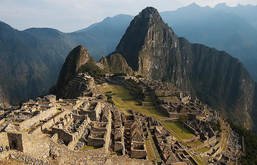 Tourists, dwarfed by the ruins and Huayna Picchu mountain, walk into  Machu Picchu, Peru, on September 21, 2005.