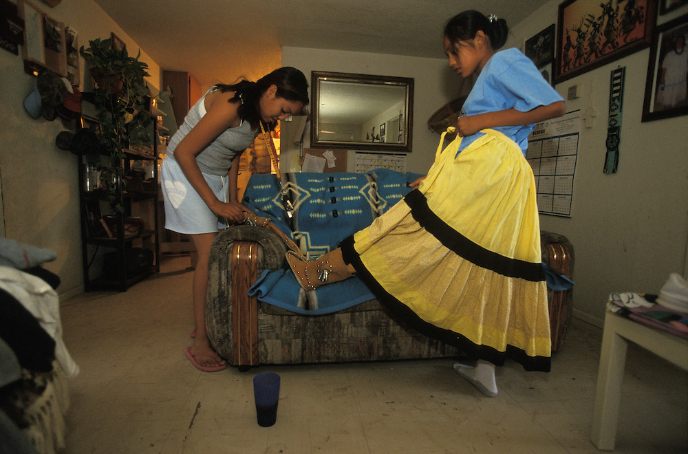 An Apache girl puts on her camp dress and moccasins in her home on the San Carlos Apache Indian Reservation in Arizona, USA. June 2004. Her sister helps her with the moccasins.