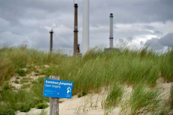 Nederland, The Netherlands, Wijk aan zee, 12-6-2018Duinen met helmgras en een waarschuwingsbord van het hoogheemraadschap . Op de achtergrond schoorstenen van de hoogovens van tatasteel, thyssenkrupp .Foto: Flip Franssen