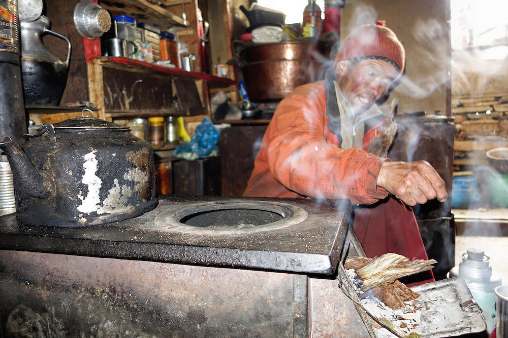 Lama in a small kitchen at Mu Gompa monastery, Tsum Valley, Nepal.