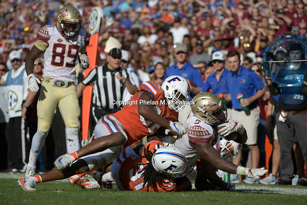 Florida State running back Jacques Patrick (9) is tackled by Florida defensive lineman Jabari Zuniga (92), left, defensive back Shawn Davis (31) and cornerback Marco Wilson (3), right, after rushing for yardage during the second half of an NCAA college football game Saturday, Nov. 25, 2017, in Gainesville, Fla. FSU won 38-22. (Photo by Phelan M. Ebenhack)
