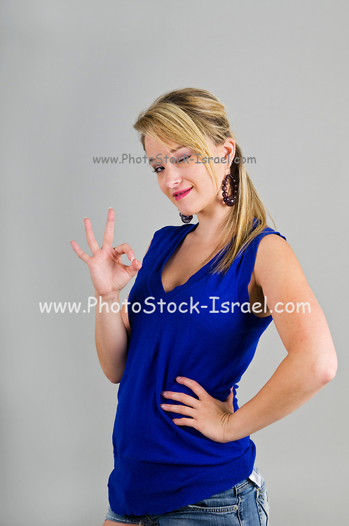Young blond female teen in blue casual top gives the OK sign