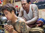 """27 MAY 2015 - BANGKOK, THAILAND: AJARN NENG ONNUT, blesses the tattoos of a Thai man who came to Ajarn Neng's home. Ajarn Neng is a revered master of sacred tattoos and sees people all day at his Bangkok home. Sak Yant (Thai for """"tattoos of mystical drawings"""" sak=tattoo, yantra=mystical drawing) tattoos are popular throughout Thailand, Cambodia, Laos and Myanmar. The tattoos are believed to impart magical powers to the people who have them. People get the tattoos to address specific needs. For example, a business person would get a tattoo to make his business successful, and a soldier would get a tattoo to help him in battle. The tattoos are blessed by monks or people who have magical powers. Ajarn Neng, a revered tattoo master in Bangkok, uses stainless steel needles to tattoo, other tattoo masters use bamboo needles. The tattoos are growing in popularity with tourists, but Thai religious leaders try to discourage tattoo masters from giving tourists tattoos for ornamental reasons.     PHOTO BY JACK KURTZ"""