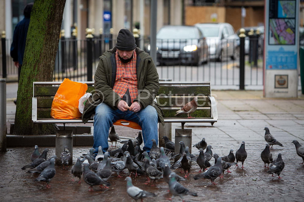 A man wearing a mask on his chin sits on a public bench in Folkestone town centre feeding bread to pigeons on the 27th of January 2021 in Folkestone, United Kingdom.