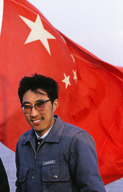 A member of the chinese communism parti happy to be captured before the chinese flag. On the boat to Shanghai.